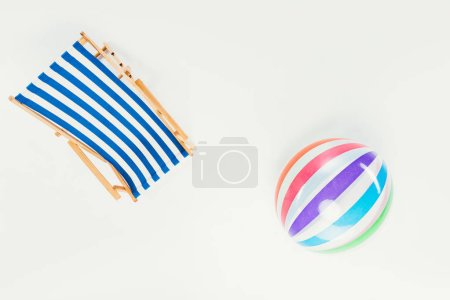 top view of striped beach chair and inflatable beach ball isolated on white