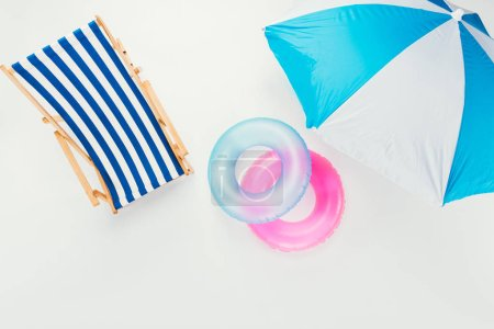 top view of beach umbrella, striped beach chair and inflatable rings isolated on white