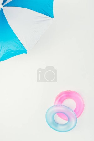 top view of beach umbrella and inflatable rings isolated on white