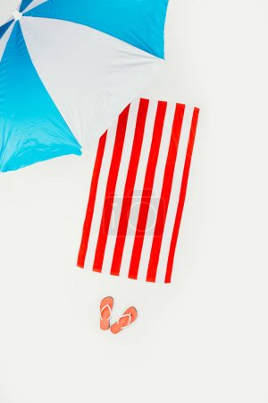top view of beach umbrella, striped towel and flip flops isolated on white