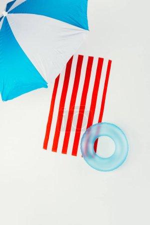 Photo pour Vue du haut du parasol, serviette rayée et anneau gonflable isolé sur blanc - image libre de droit
