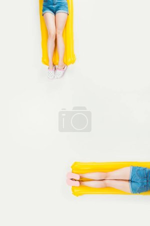 partial top view of people lying on swimming mattresses isolated on white