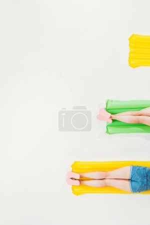 cropped shot of people resting on inflatable mattresses isolated on white