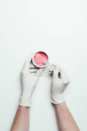 cropped shot of woman in latex gloves taking pink mask from container by spoon on white surface