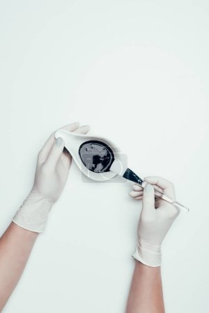 cropped shot of woman in latex gloves holding black mask and brush isolated on white surface