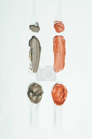 flat lay with spoons and various colorful clay mask smudges placed in row isolated on white surface