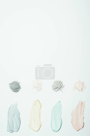 flat lay with different clay powder and colorful clay mask smudges placed in row isolated on white surface