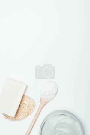 flat lay with soap, sponge, spoon, clay mask in container and clay powder isolated on white surface