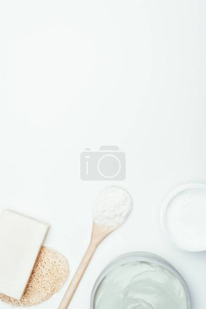 flat lay with soap, sponge, spoon, clay masks in containers and clay powder isolated on white surface