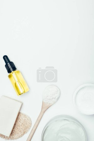 flat lay with soap, sponge, spoon, clay masks in containers, cosmetic bottle with pipe and clay powder isolated on white surface