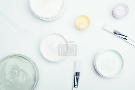 flat lay with different clay masks in containers and brushes isolated on white surface