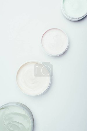 flat lay with different clay masks in containers placed in row isolated on white surface