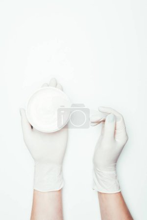 cropped image of woman in latex gloves holding container with clay mask and spoon isolated on white