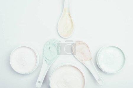 Photo pour Pose plate avec divers masques en argile colorée dans des récipients et des cuillères isolés sur une surface blanche - image libre de droit
