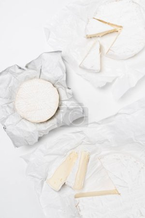 top view of various brie cheese heads on crumpled paper and on white surface