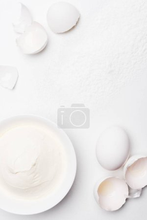 top view of sour cream in bowl and cracked egg shells on white surface spilled with flour