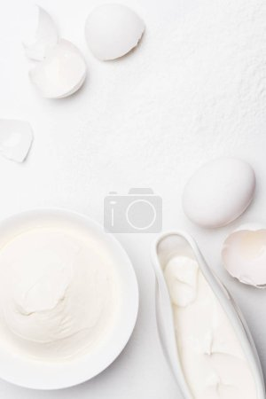 top view of sour cream and cracked egg shells on white surface spilled with flour