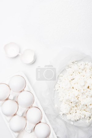 top view of homemade cottage cheese and eggs on white surface