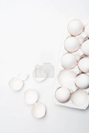 top view of raw chicken eggs in carton on white surface