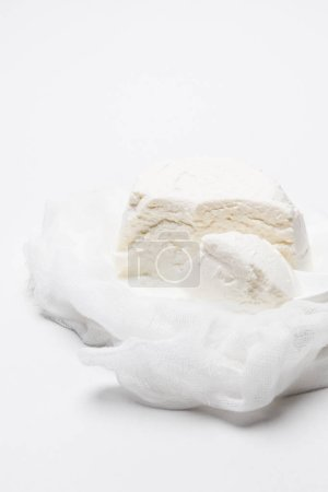 delicious cottage cheese on cheesecloth with spoon on white tabletop