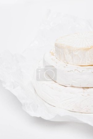 stack of delicious brie cheese heads on crumpled paper and on white surface
