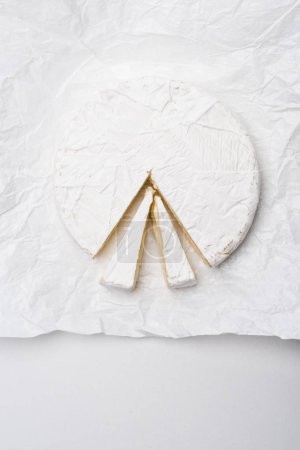 top view of sliced brie cheese on crumpled paper and on white surface