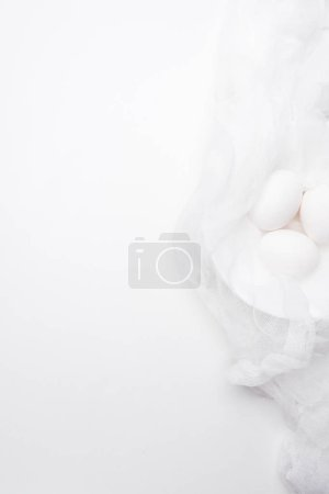 top view of chicken eggs in cheesecloth on white surface