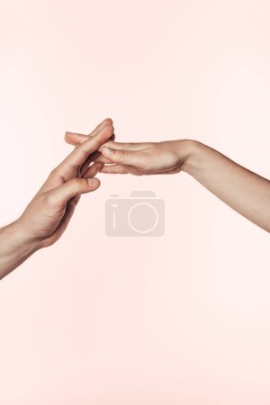 cropped image of woman and man joining hands isolated on pink background