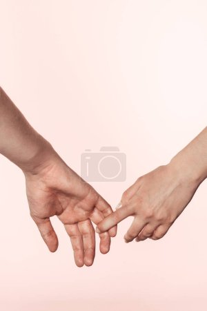 cropped shot of woman holding man hand by finger isolated on pink background