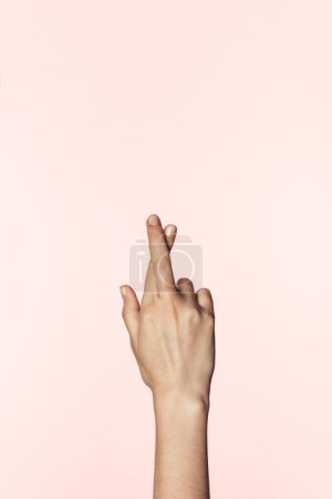 partial view of woman doing crossed fingers gesture isolated on pink background