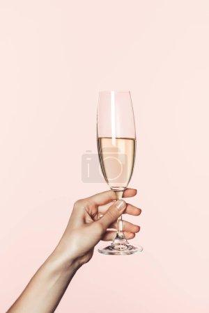 Photo pour Vue partielle de la femme tenant le verre de champagne isolé sur fond rose - image libre de droit