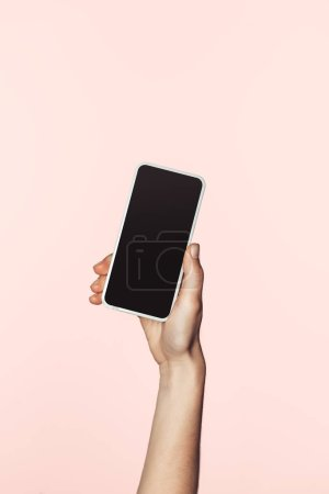 cropped image of woman holding smartphone with blank screen isolated on pink background