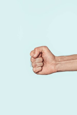 Photo for Cropped image of male fist isolated on blue background - Royalty Free Image