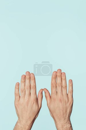 cropped image of male hands isolated on blue background