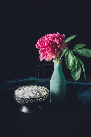 peony flower in vase and vintage bowl with sweet marshmallows on dark background