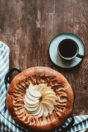 Photo for Top view of homemade apple pie and cup of coffee on wooden tabletop - Royalty Free Image