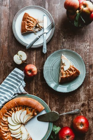 flat lay with pieces of apple pie on plates, cutlery and fresh apples on wooden tabletop