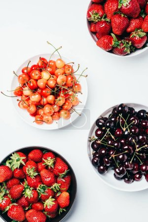 top view of fresh ripe tasty summer berries in bowls on white