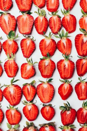 top view of seamless pattern made of ripe fresh sliced strawberries on white