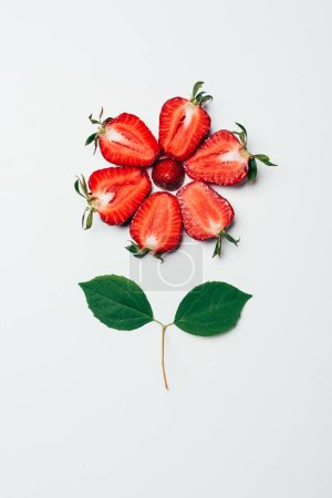 top view of flower made of sliced strawberries and green leaves on white
