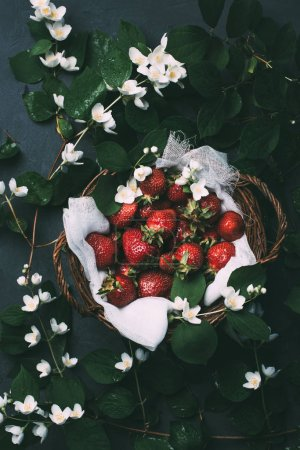 top view of beautiful jasmine flowers and sweet ripe strawberries in basket