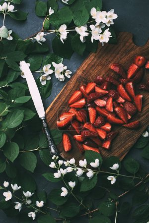 top view of beautiful jasmine flowers, sliced strawberries on wooden cutting board and knife