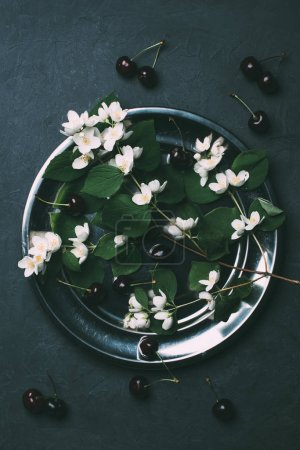 Photo for Top view of beautiful white jasmine flowers and ripe sweet cherries on black - Royalty Free Image