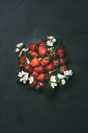 top view of fresh ripe strawberries and jasmine flowers on black