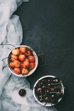 Photo pour Vue de dessus des cerises dans des bols sur fond noir - image libre de droit