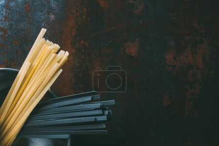 top view of black and classical linguine pasta in pan on rustic table