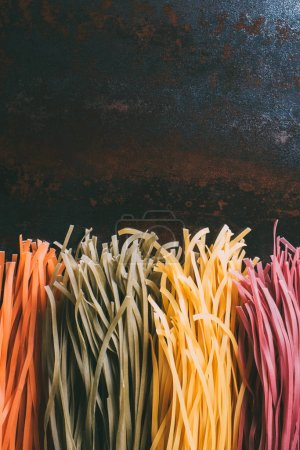 elevated view of arranged colorful tagliatelle pasta placed in row on metal table