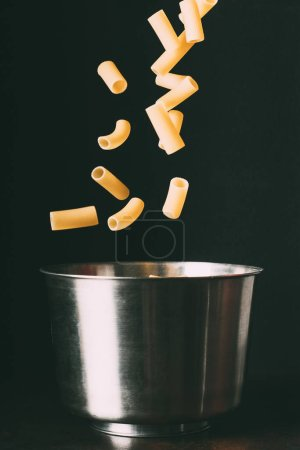 close up view of rigatoni falling into pan on black background