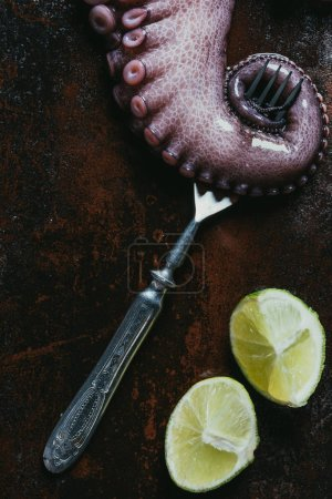 top view of big octopus tentacle with fork and limes on rusty metal surface