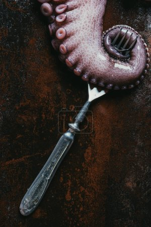 Photo for Top view of big octopus tentacle with fork on rusty metal surface - Royalty Free Image